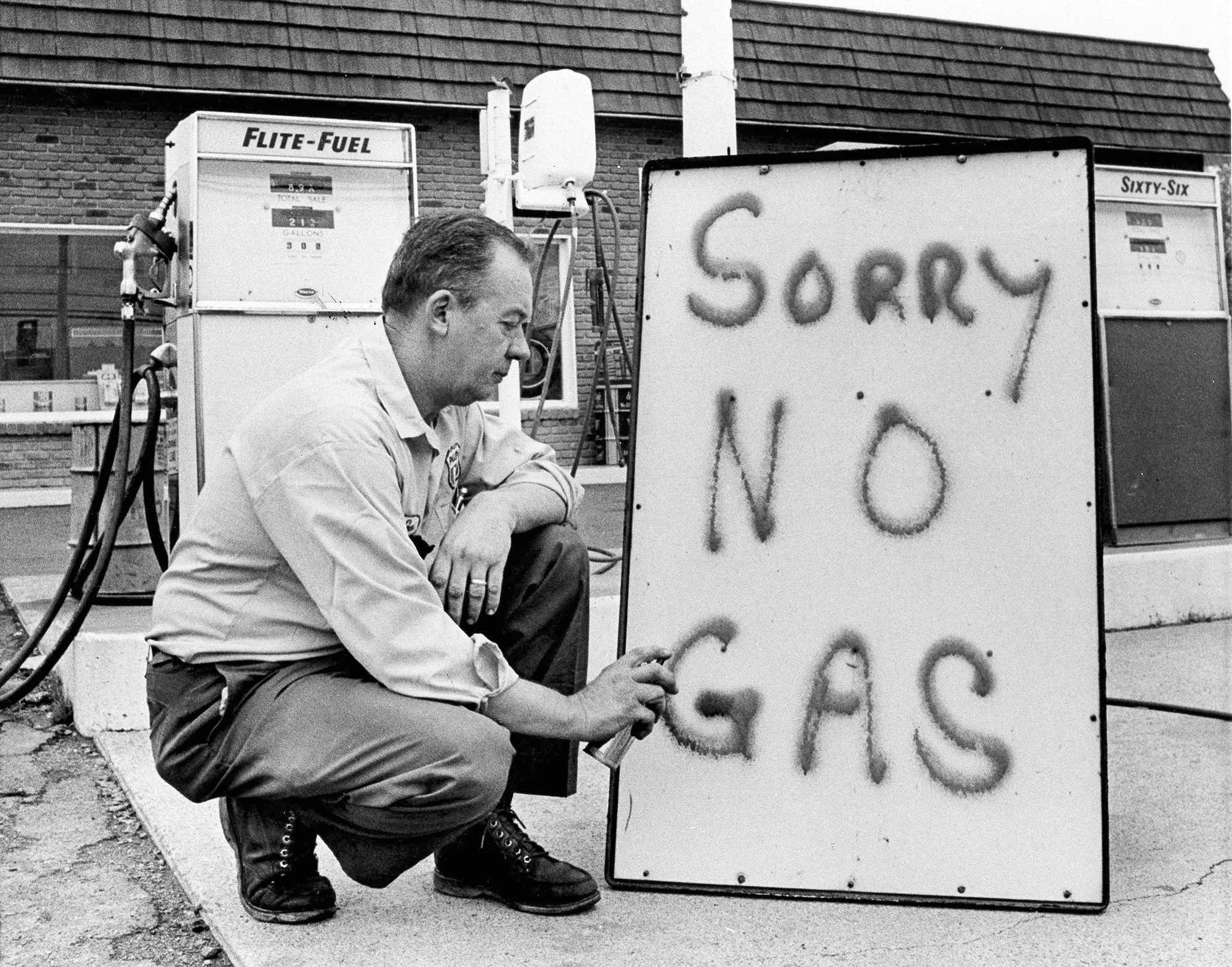 """Black-and-white photo of a man spray-painting """"Sorry No Gas"""" on a sign."""