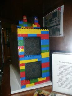 Image of large lego blocks make up a 3 foot tall housing for a computer with two screens.