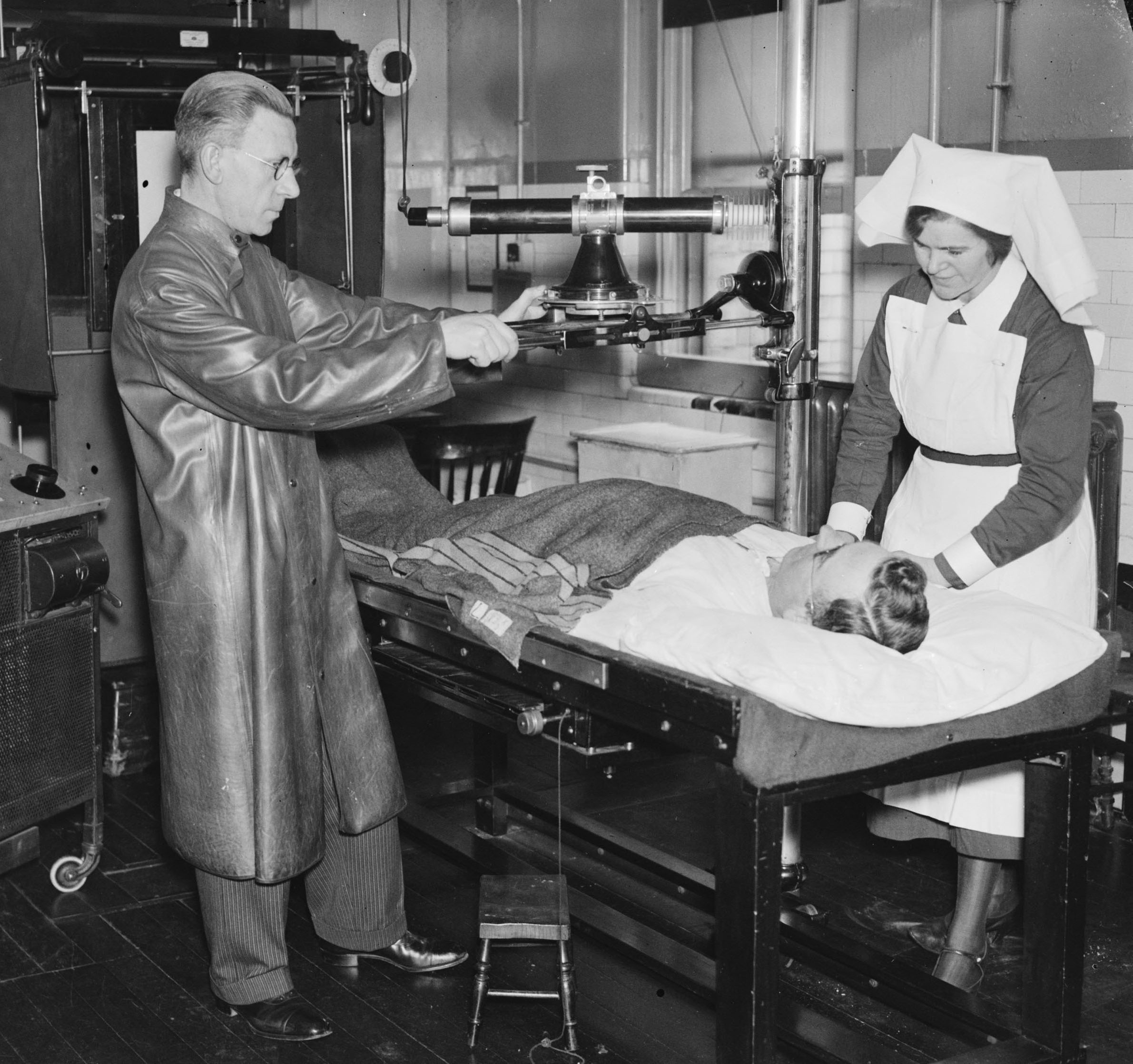 1932 photograph of staff taking an X-ray of a patient at Charing Cross Hospital, London. As a nurse makes the patient comfortable, the radiologist, in heavy protective clothing, sets up the X-ray machine.