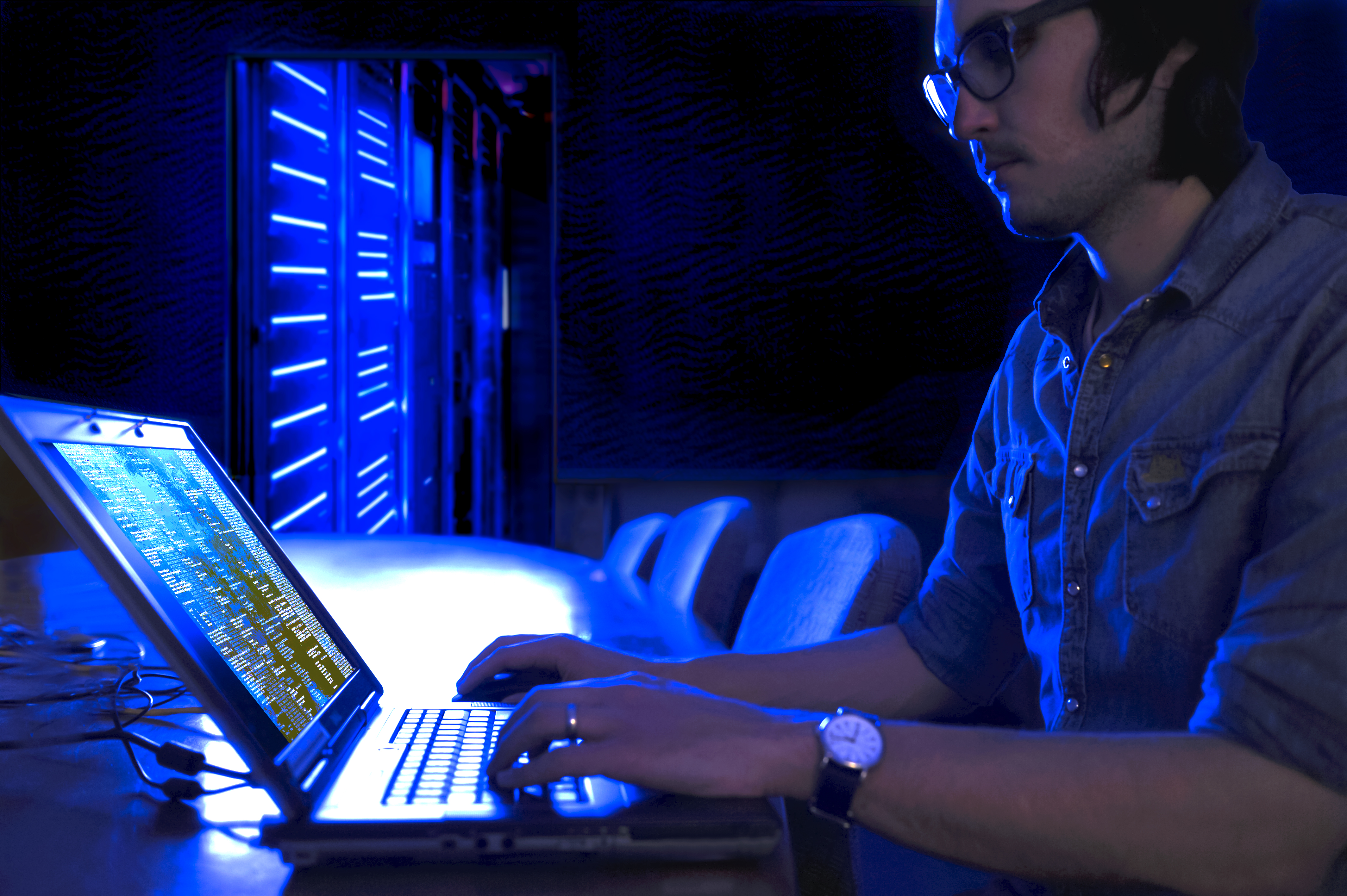 Man coding on laptop surrounded in a glow of blue light.