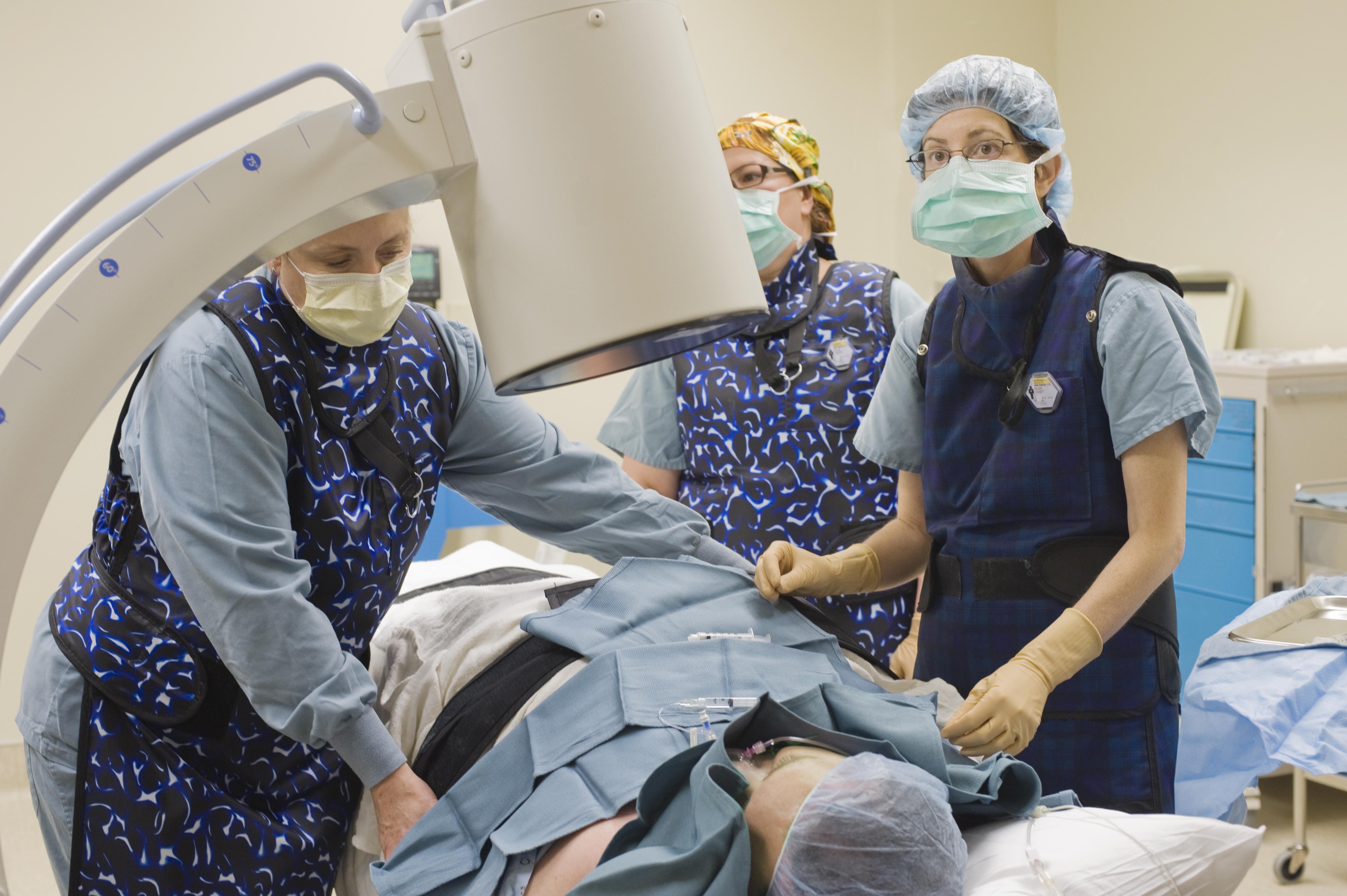 Surgeon and team position patient under xray machine.