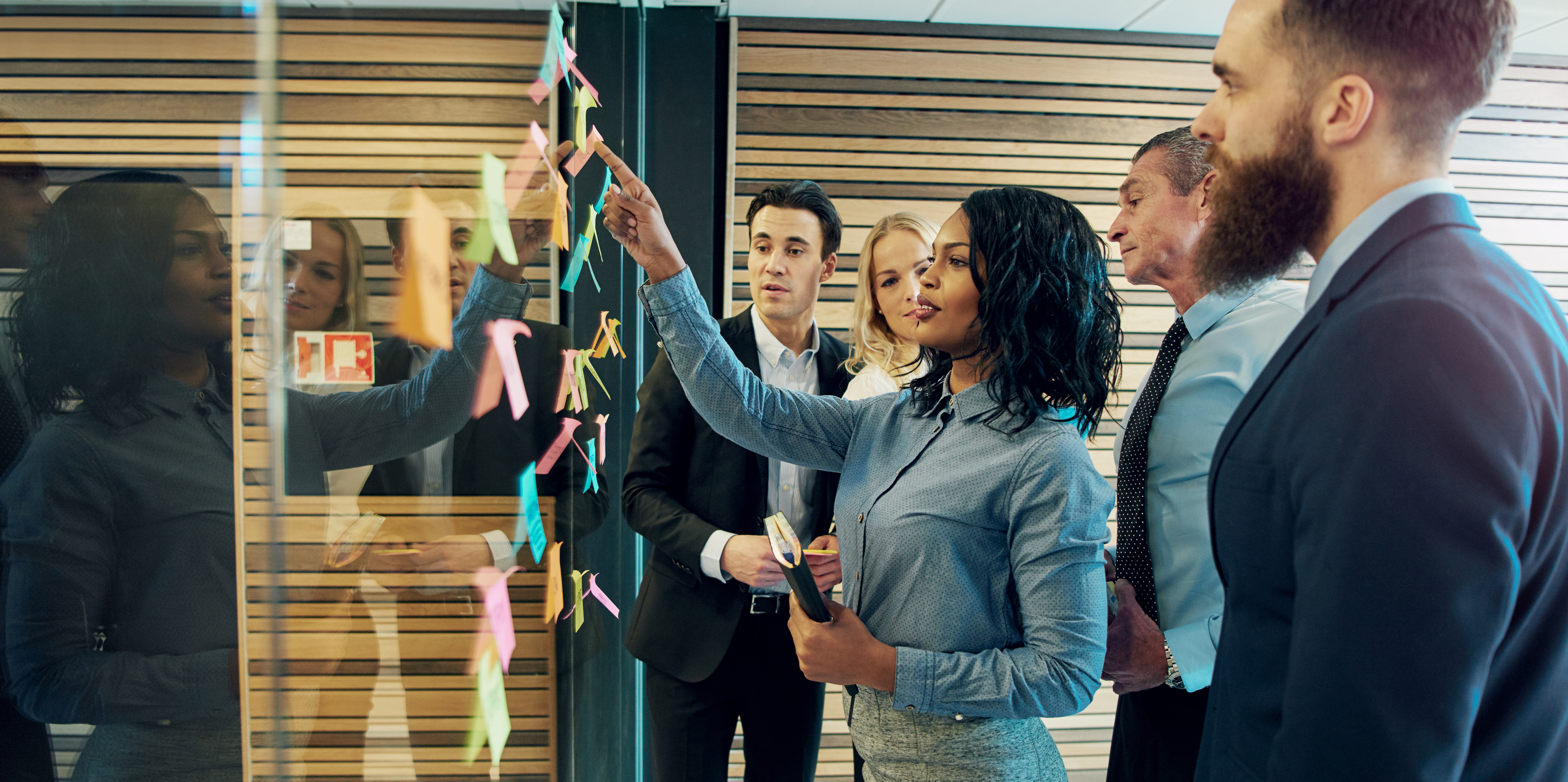 Creative group of business people brainstorming putting sticky notes on glass wall in office.