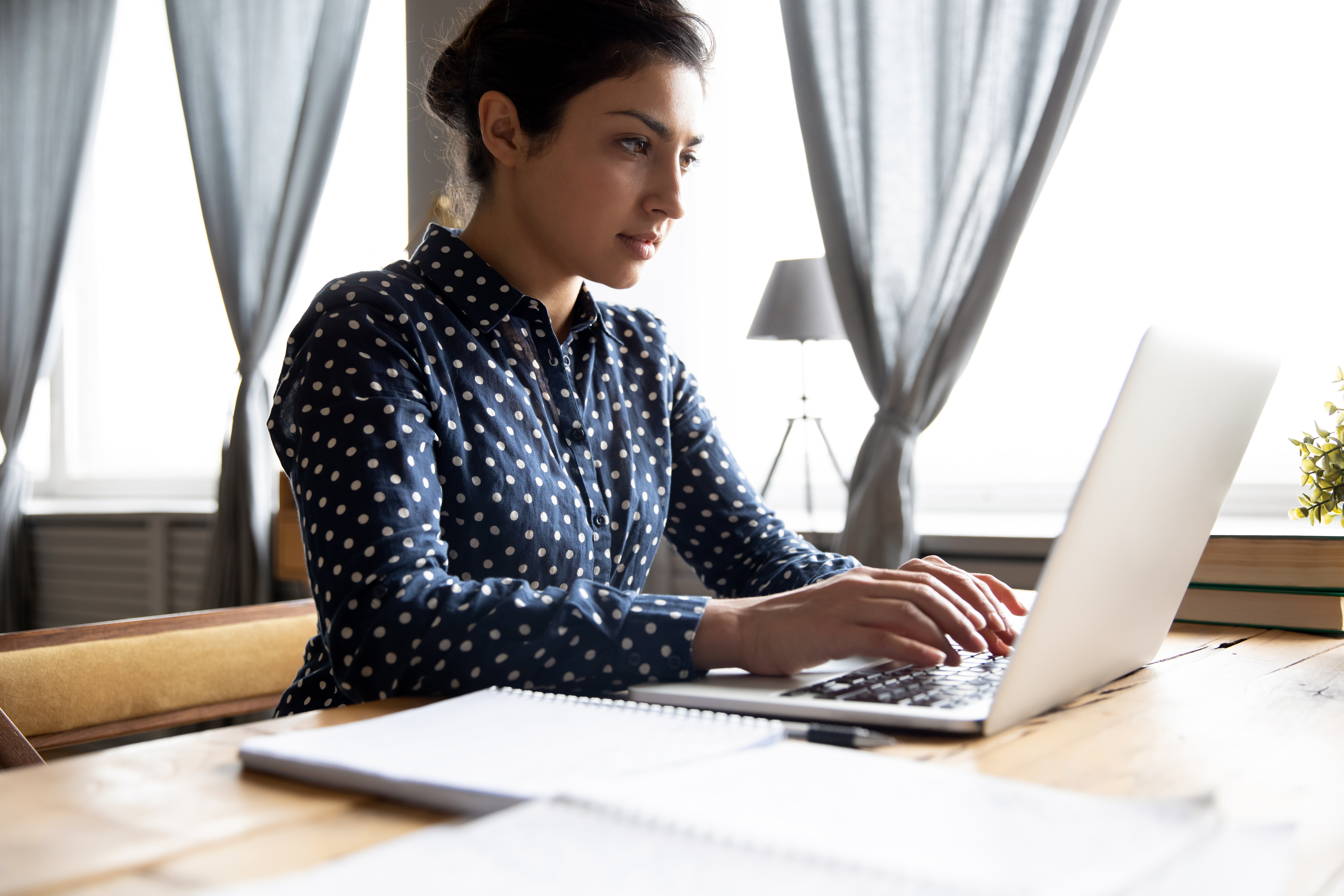 Photograph of a woman looking typing on computer