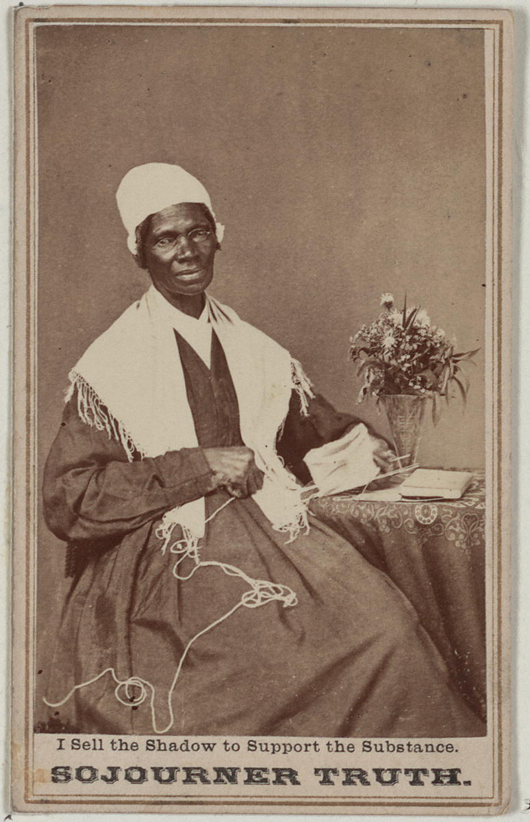 Black-and-white photograph of Sojourner Truth seated by a small table