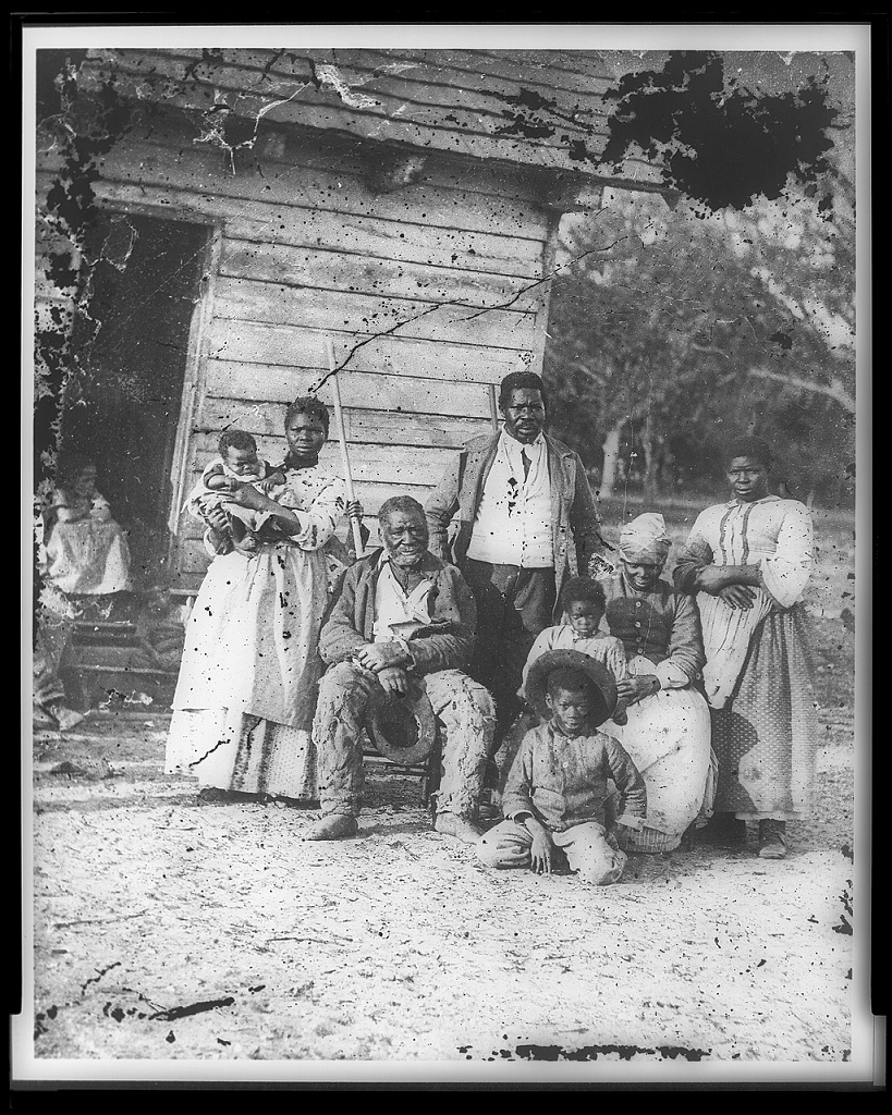 Black-and-white photograph of eight Black people sitting or standing as they pose outside a small, simple building