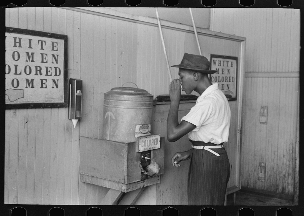 "Black-and-white photograph of a Black man drinking water as he stands in front of a water cooler labeled ""Colored"""