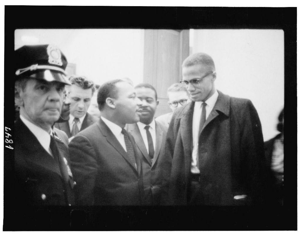 Black-and-white photograph of Martin Luther King, Jr., and Malcom X speaking, as several people stand around and behind them