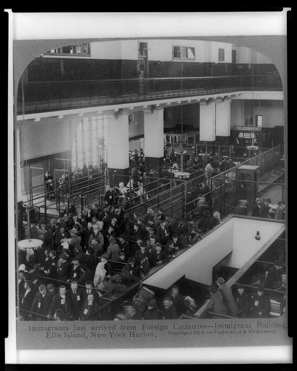 Black-and-white photograph of many people sitting on benches inside a great hall, with an American flag displayed from the balcony