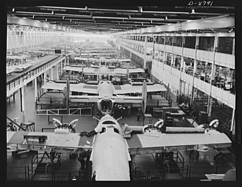 Black-and-white photograph of many planes lined up inside a factory, with a few people working on them.