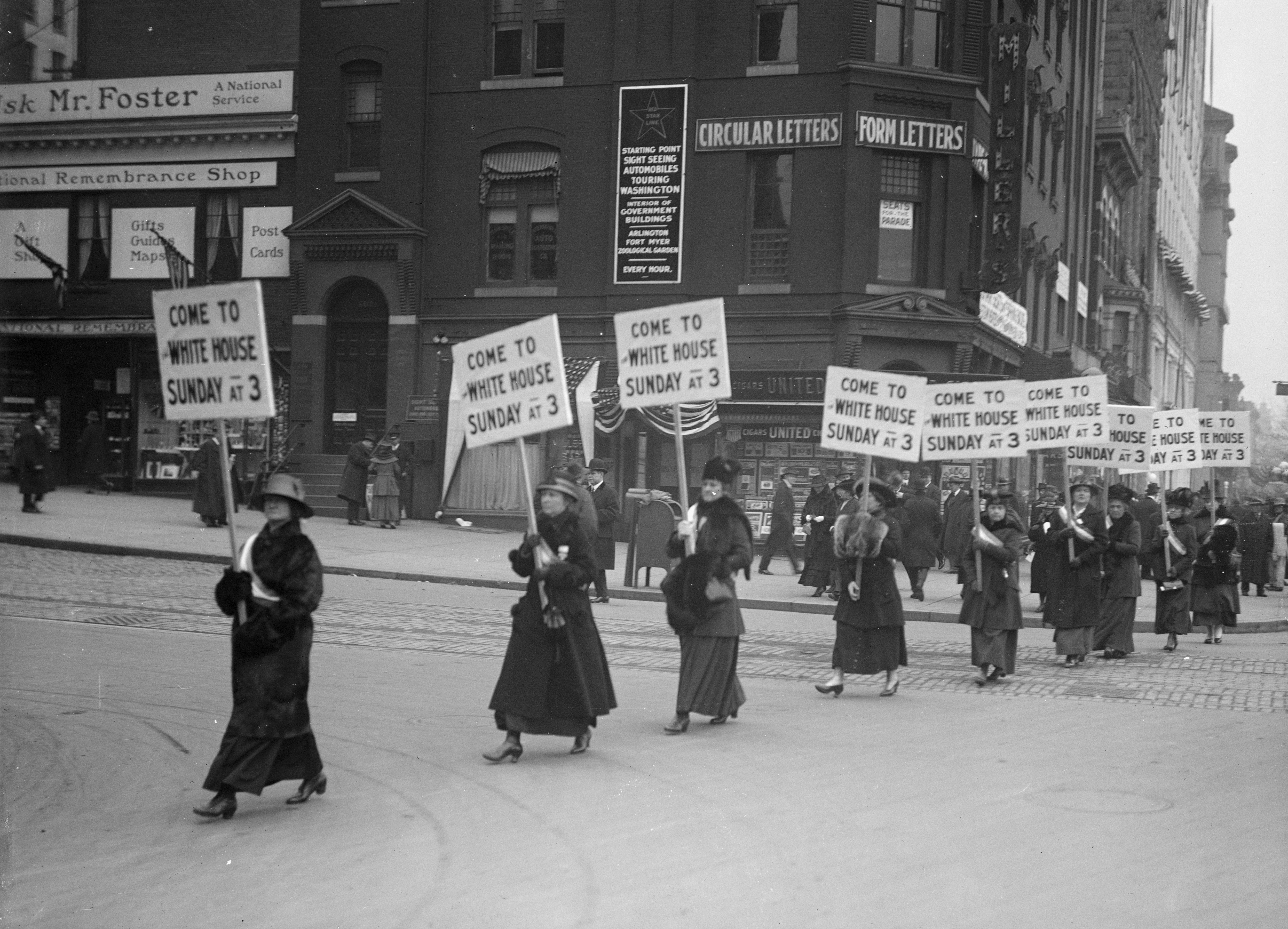 "Black-and-white photograph of a line of women crossing a street while holding signs that read, ""Come to White House Sunday at 3"""