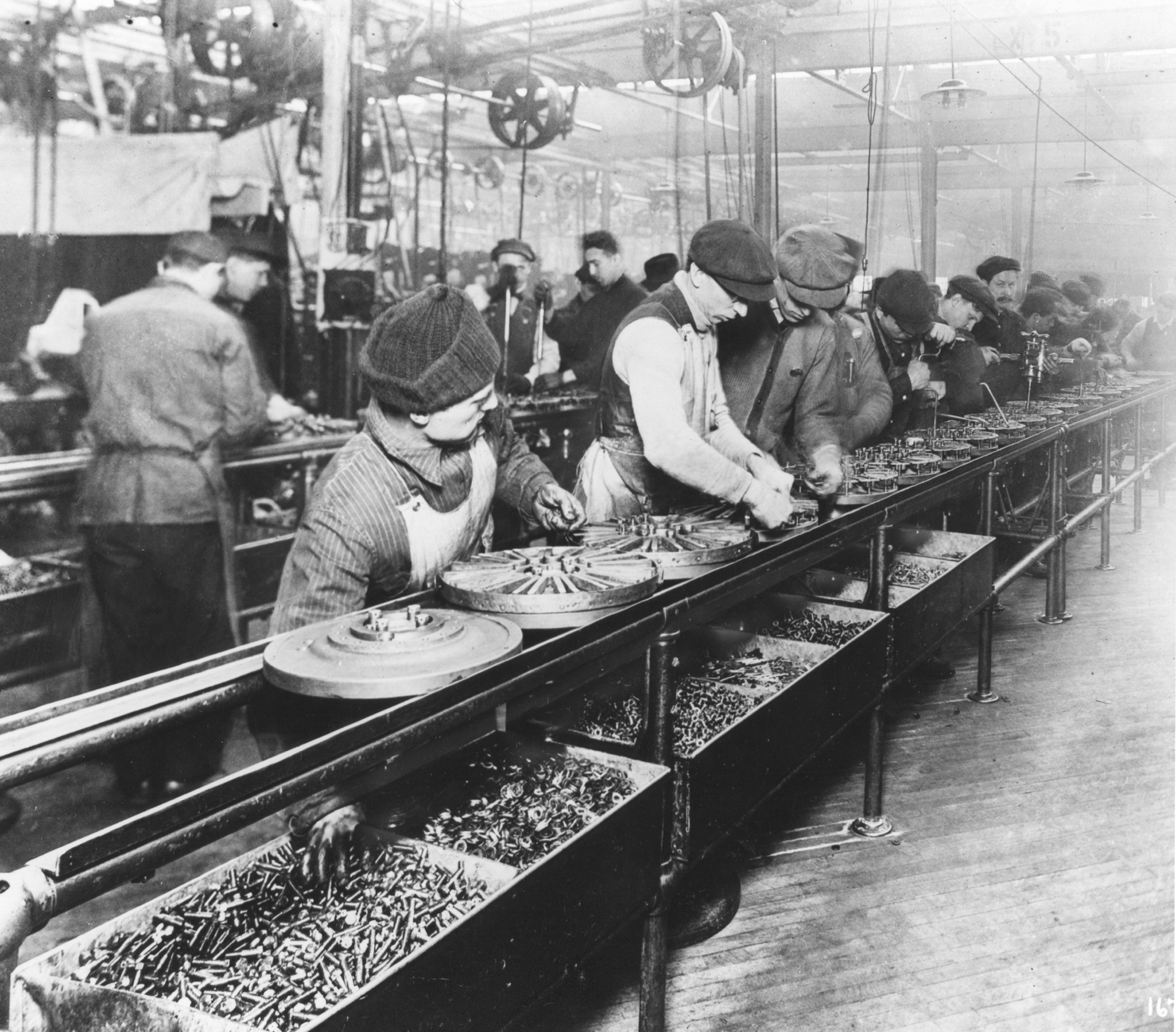 Workers in asembly line putting together magnetos and flywheels for 1913 Ford automobiles.