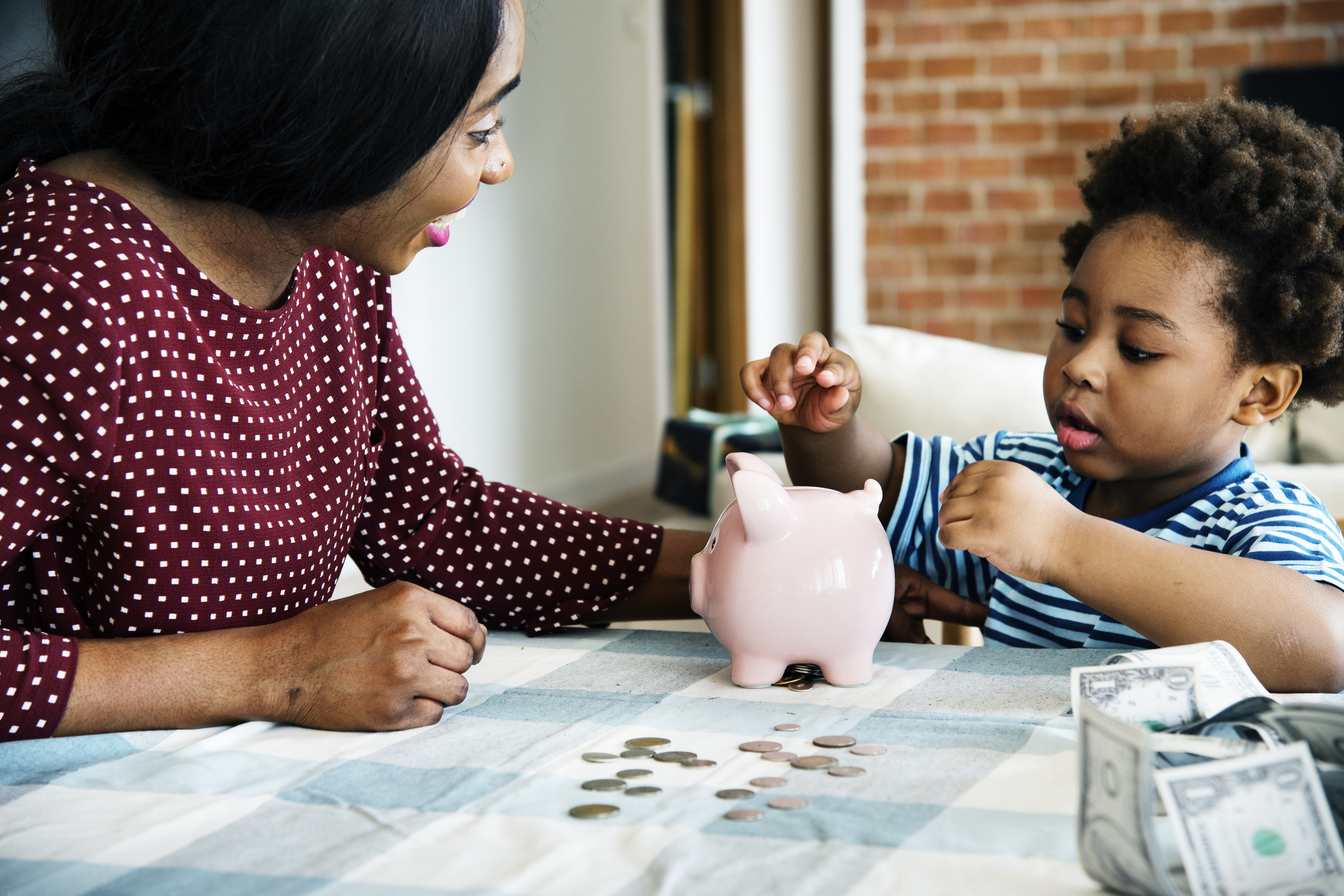 a mother and her son placing coins in a piggy bank