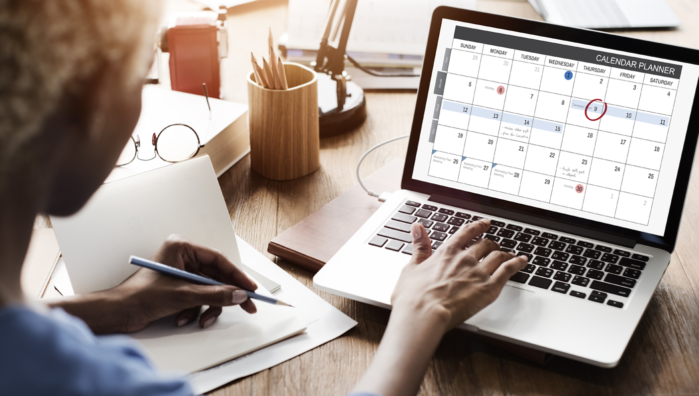 Woman at Desk on Computer Looking at Calendar