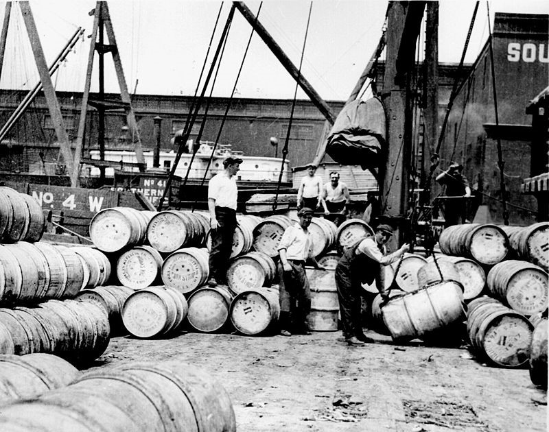 In 1912, Lewis Hine photographed these common laborers loading barrels onto a barge in New York City.