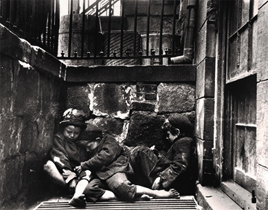 In this 1890 photograph, taken by Riis, shows a group of children sleeping near Mulberry Street.
