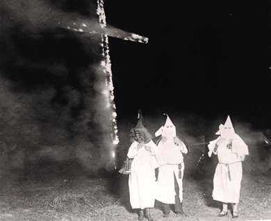 This 1921 photograph from the Denver News shows three members of the Ku Klux Klan (two women and one man) standing in front of a burning cross.
