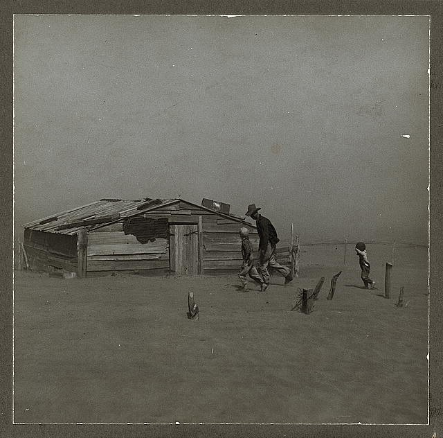 """Photograph titled """"Farmer and sons walking in the face of a dust storm. Cimarron County, Oklahoma"""", taken by Arthur Rothstein in April 1936."""