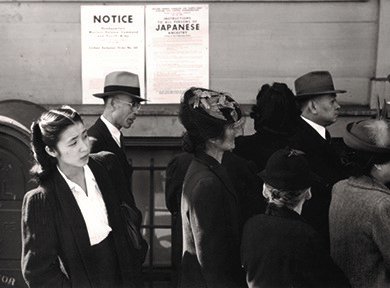 Japanese Americans standing in line in front of a poster detailing internment orders in California.