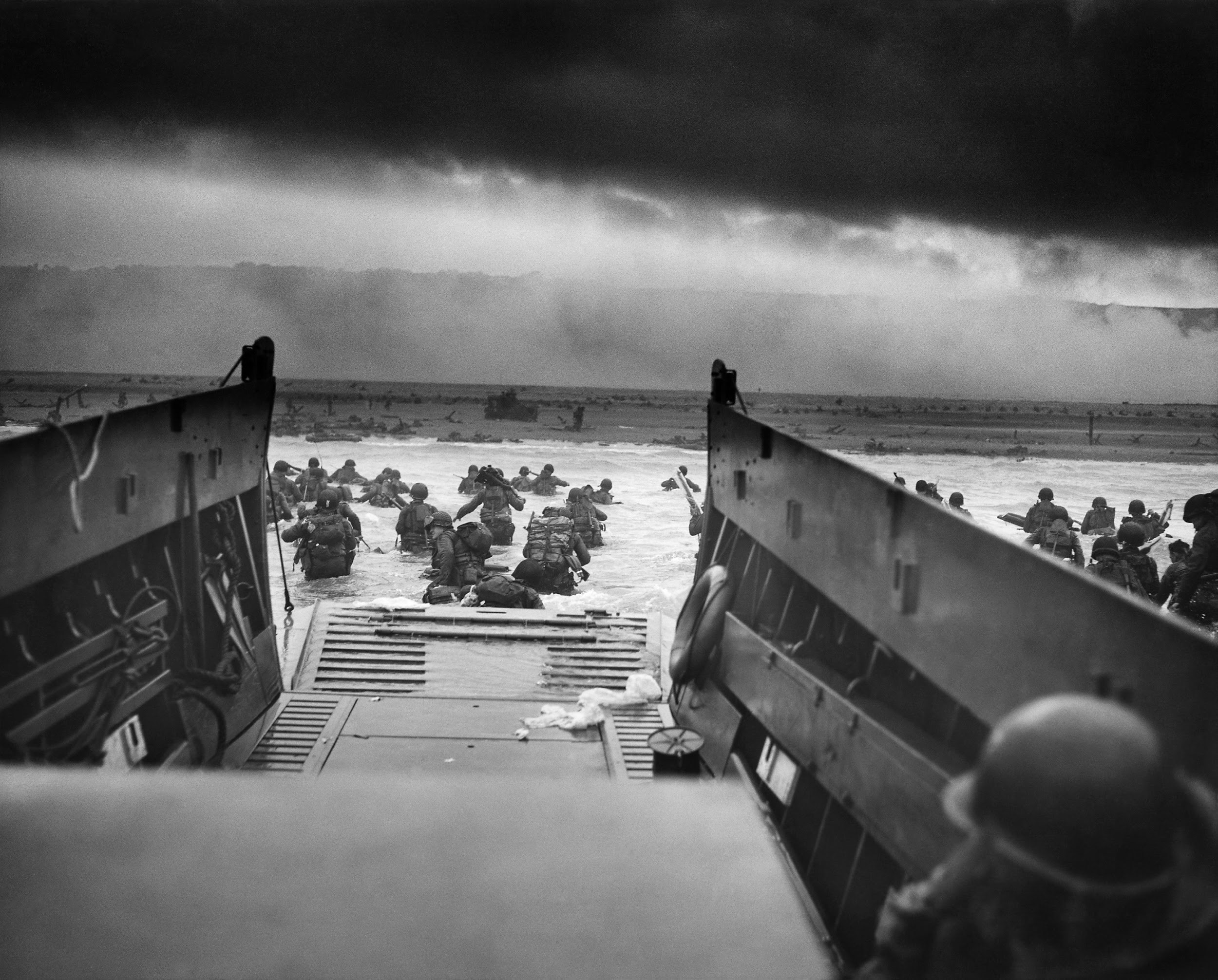 """One of the most-reproduced photographs of D-Day, """"Into the Jaws of Death"""" by Robert F. Sargent, shows American soldiers exiting a landing craft and wading ashore on an area of the Normandy coast designated """"Omaha Beach"""" on the morning of D-Day."""