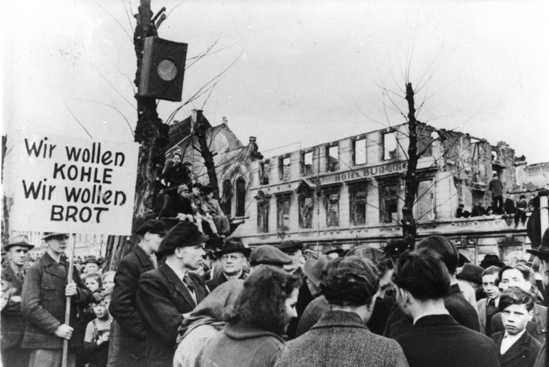 """Hungry civilians in West Germany protest the lack of food and other supplies in March of 1947.  The sign reads """"We want COAL, We want BREAD."""" Note the ruined building in the background and other evidence of wartime devastation."""