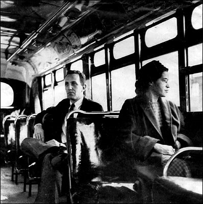 In what was likely a staged photograph, Rosa Parks sits at the front of a bus in December of 1956, after the city of Montgomery desegregated its bus system. A reporter sits behind her.
