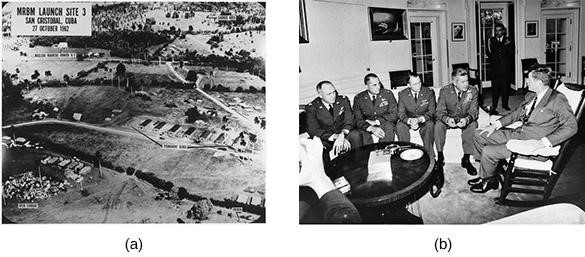 This low-level U.S. Navy photograph of San Cristobal, Cuba, shows one of the sites built to launch intermediate-range missiles at the United States (a). As the date indicates, it was taken on the last day of the Cuban Missile Crisis. Following the crisis, Kennedy met with the reconnaissance pilots who flew the Cuban missions (b). (credit a: modification of work by the National Archives and Records Administration; credit b: modification of work by the Central Intelligence Agency)