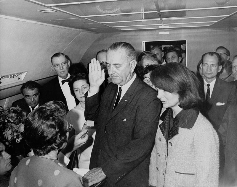 Lyndon B. Johnson (center) takes the oath of office on Air Force One, just hours after President Kennedy's assassination. Jacqueline Kennedy (right) looks on.