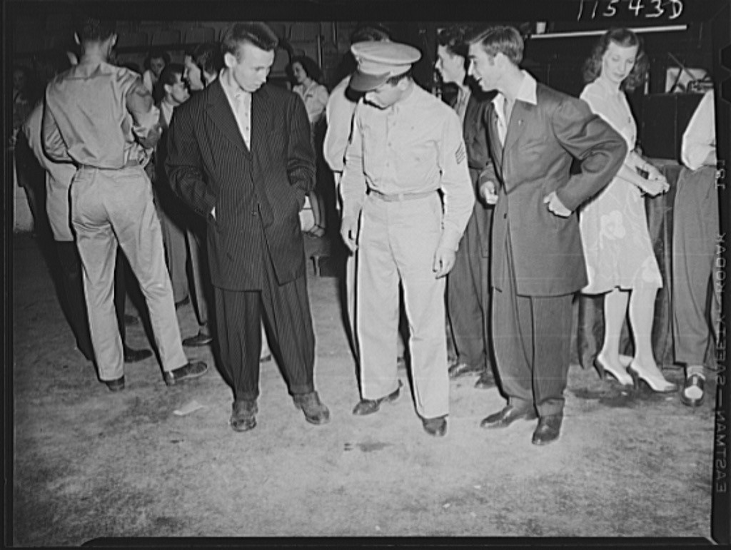 "An American soldier observes two young men wearing ""zoot suits"" at a musical performance in Washington, D.C., in 1942."