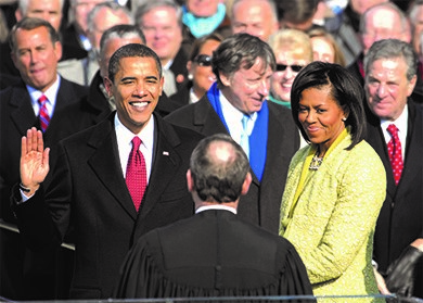 Barack Obama takes the oath of office as the 44th President of the United States. Standing next to him is First Lady Michelle Obama.