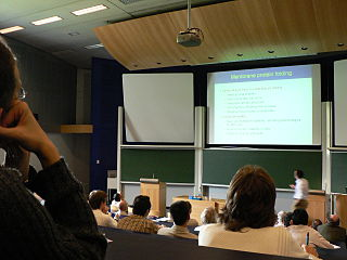 Co-Located Audience - An audience listens to a speaker in an auditorium at the University of Liège.